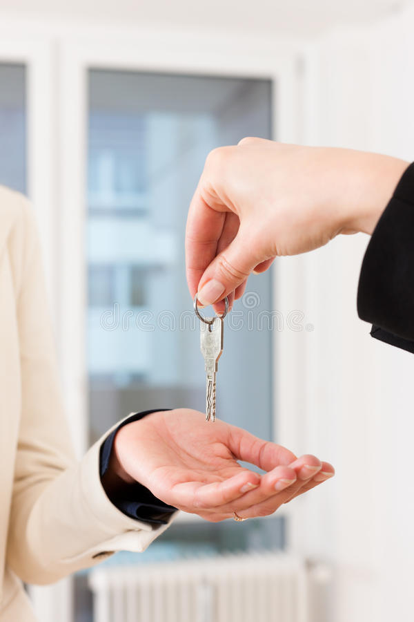 Young realtor is with keys in an apartment. Young realtor is giving the keys to an apartment to the tenant, close-up on keys and hands stock photography
