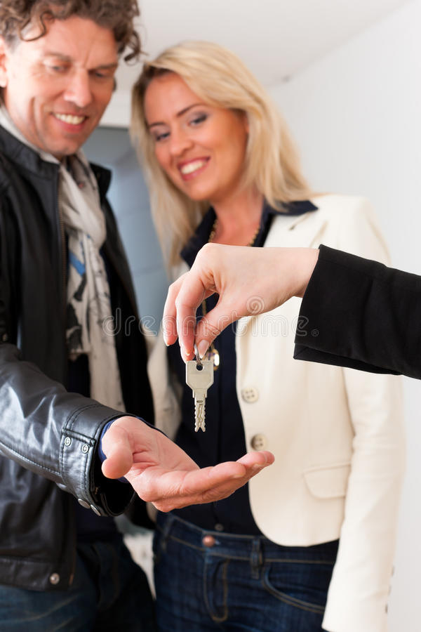 Young realtor is with keys in an apartment. Young realtor is giving the keys to an apartment to a young couple, maybe the purchaser or the tenants stock photo