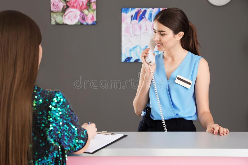 Young receptionist and client at desk. In beauty salon stock photos