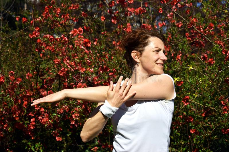 Young red hair lady is stretching her arm after outdoor training in park stock images