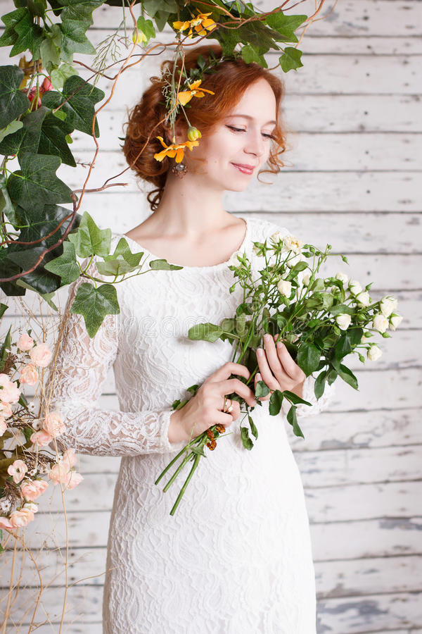 Young red-haired bride in a simple white lace dress. Is holding a bouquet of small white roses royalty free stock image