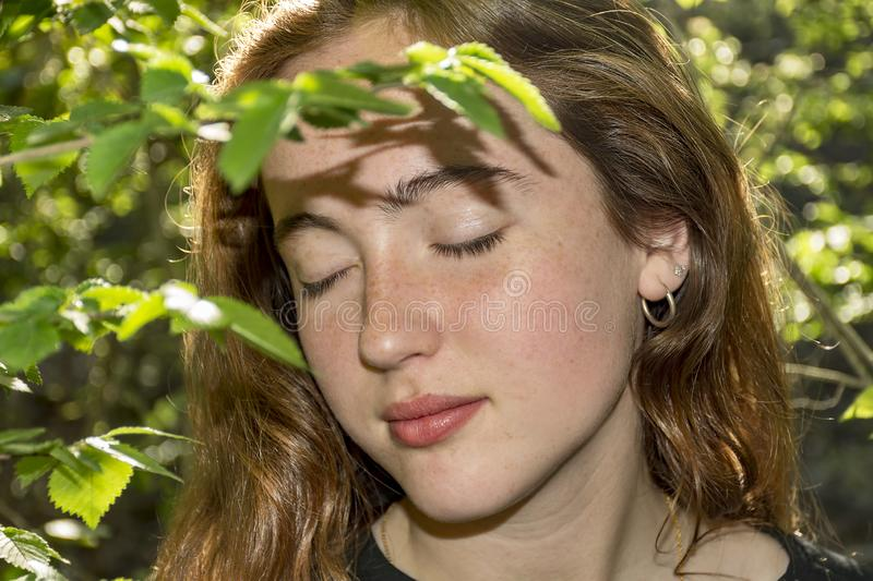 Young red-haired caucasian woman with freckles with close eyes into a forest. stock images