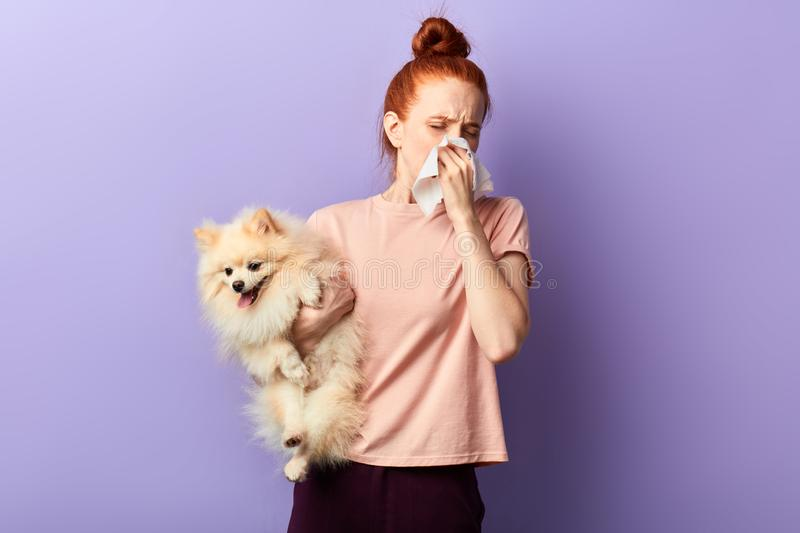 Young red-haired girl is allergic to pets. Concept of allergies to dogs. Close up portrait, studio shot, health care, treatment, medicine royalty free stock photo
