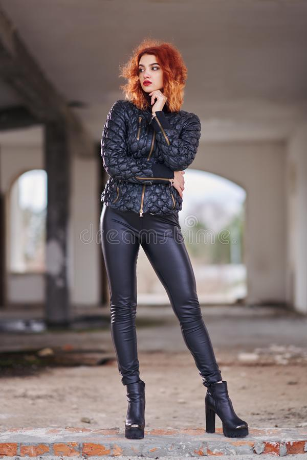 Young red-haired girl in black leather pants, platform boots and high heels, in a black jacket posing in the open air in a spaciou stock photography
