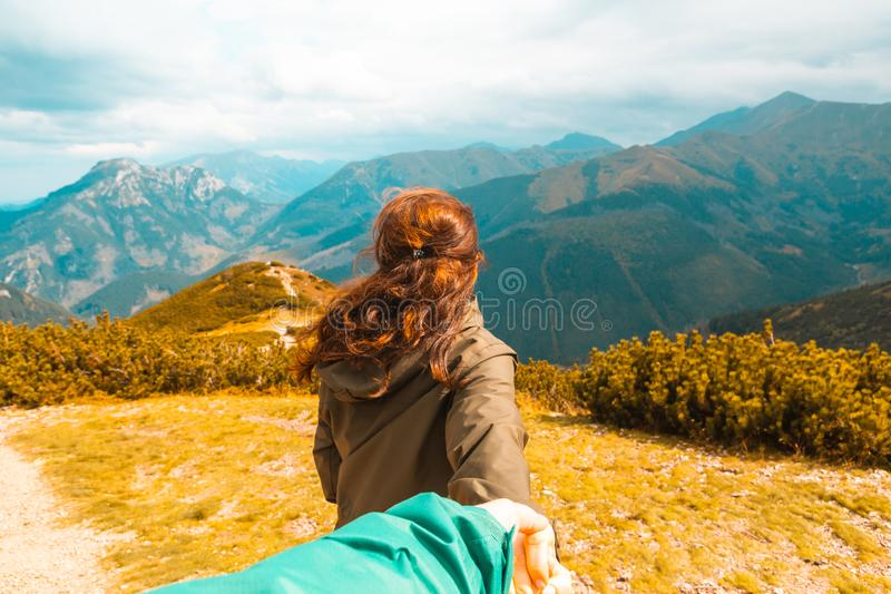 A young red-haired girl holds hands and leads a guy forward into the autumn mountains to adventure, concept follow me.  royalty free stock images