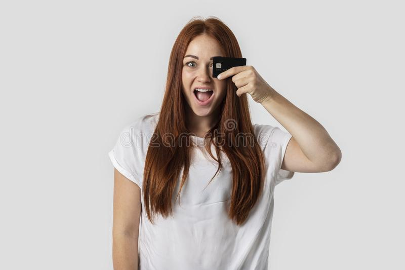 Young red-haired girl isolated on gray background in white t-shirt. She holds a credit card in her hand. The concept of shopping. In the store, cashless royalty free stock photo
