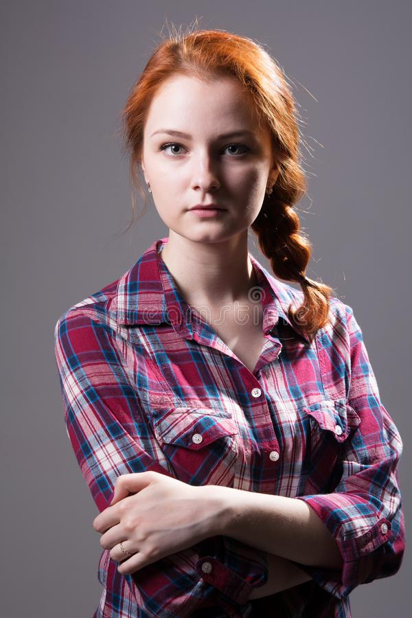 Young red-haired girl with a pigtail in a plaid shirt royalty free stock photography