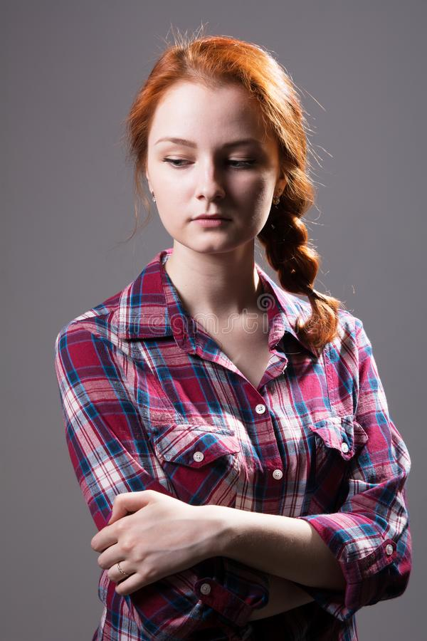 Young red-haired girl with a pigtail in a plaid shirt stock images