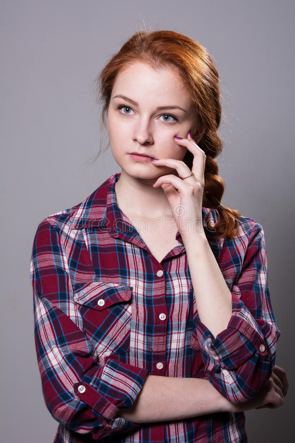 Young red-haired girl in a plaid shirt with fingers on his cheek royalty free stock photography