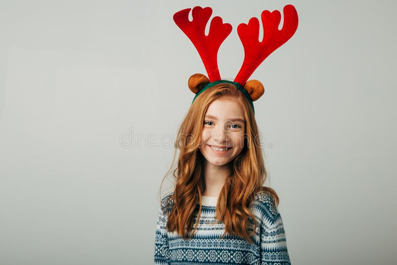 A young red-haired girl smiles and looks at the camera before Christmas. She is preparing for the celebration of the new royalty free stock photos