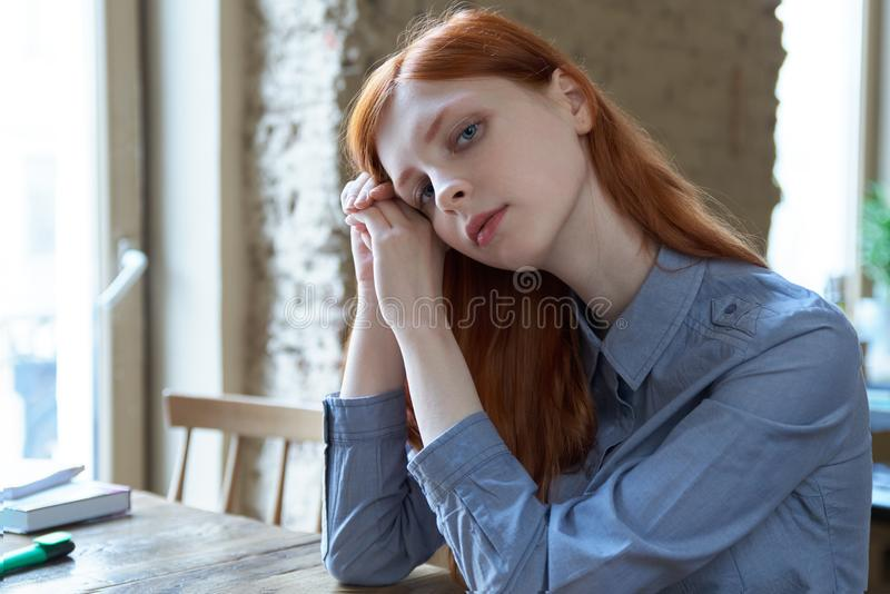 Young red-haired girl student woman preparing for exams at the c stock photo