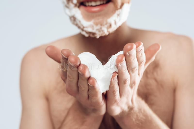 Young red haired guy smears shaving cream stock images