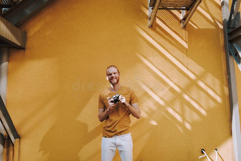 Young red haired man with photo camera. Urban lifestyle concept. Waist up portrait of young attractive happy smiling guy staying with photo camera on yellow wall stock photos