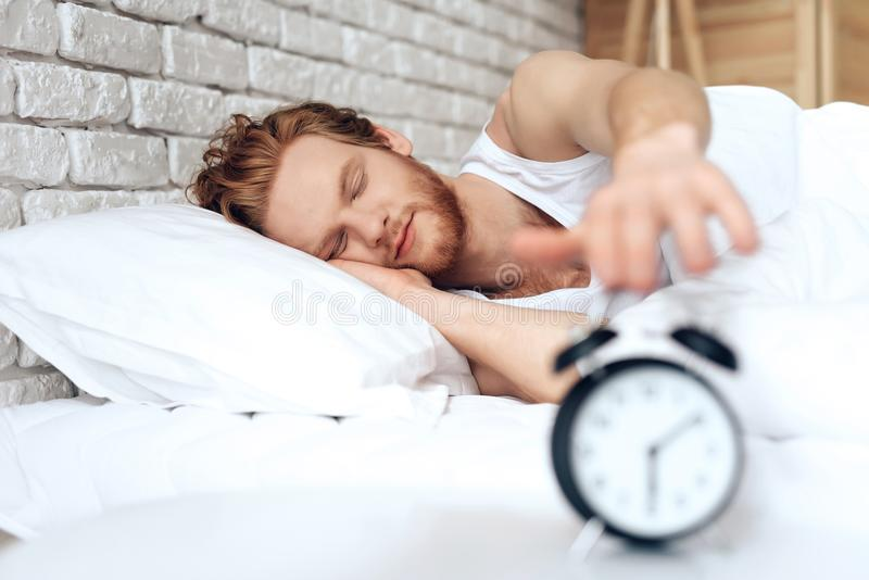 Young red haired man reaches out to turn off royalty free stock image
