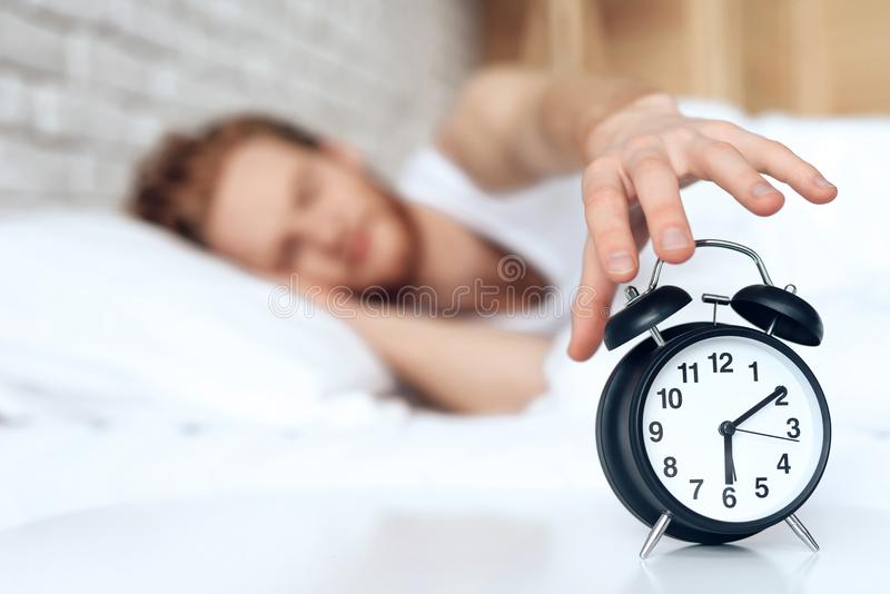 Young red haired man reaches out to turn off stock photo