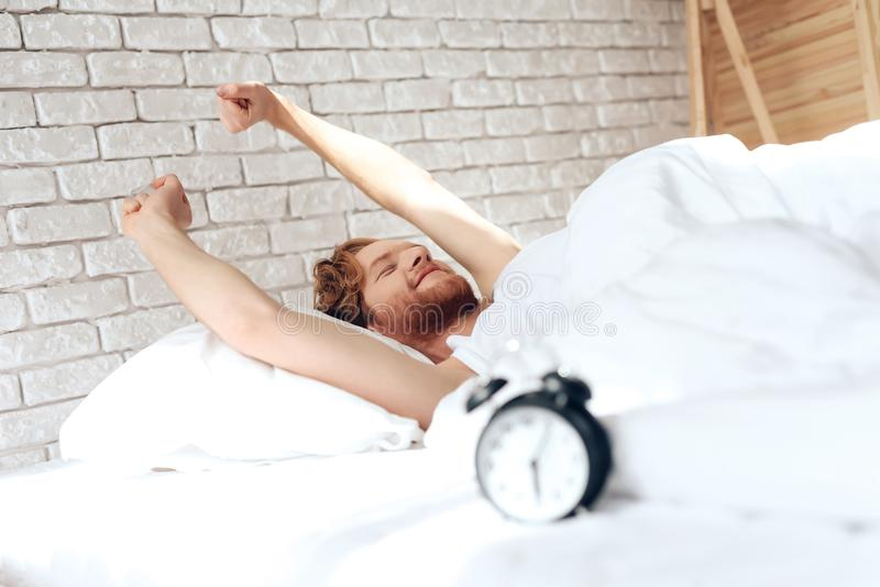 Young red haired man stretches out in bed. royalty free stock image