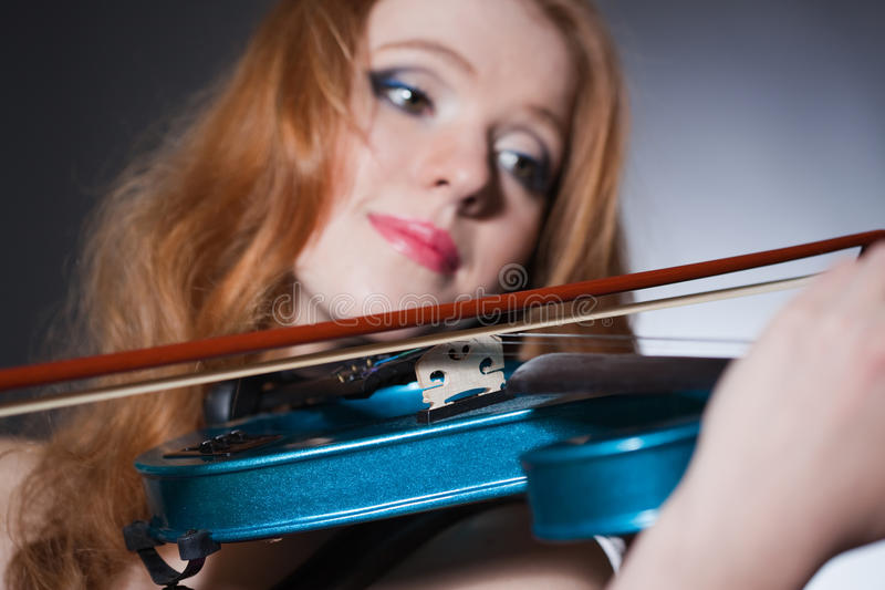 Young red-haired musician with blue violin. Closeup portrait of a young red-haired musician; unusual blue violin in focus royalty free stock photo