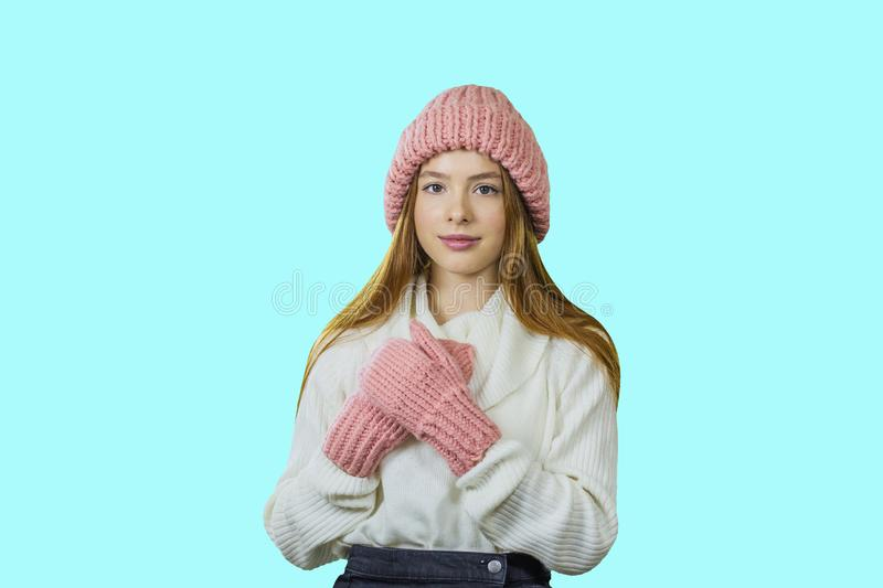 Young red-haired teenager girl in a knitted pink hat and mittens with folded arms looking at the camera, girl`s emotions stock image