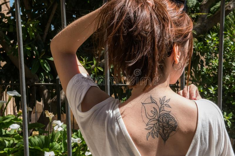 A young red-haired tourist with an Arum-lily tattoo on her back looks at a garden with the same flowers in Caceres. A young red-haired tourist with an original stock photography