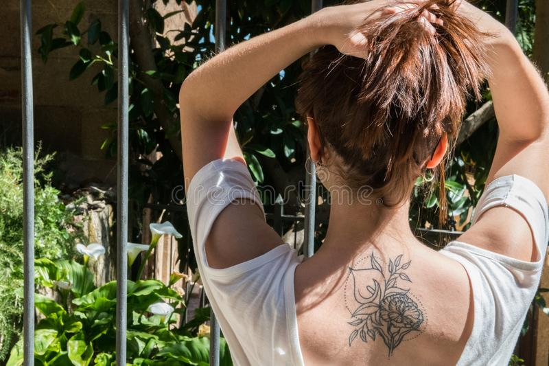 A young red-haired tourist with an Arum-lily tattoo on her back looks at a garden with the same flowers in Caceres. A young red-haired tourist with an original royalty free stock image
