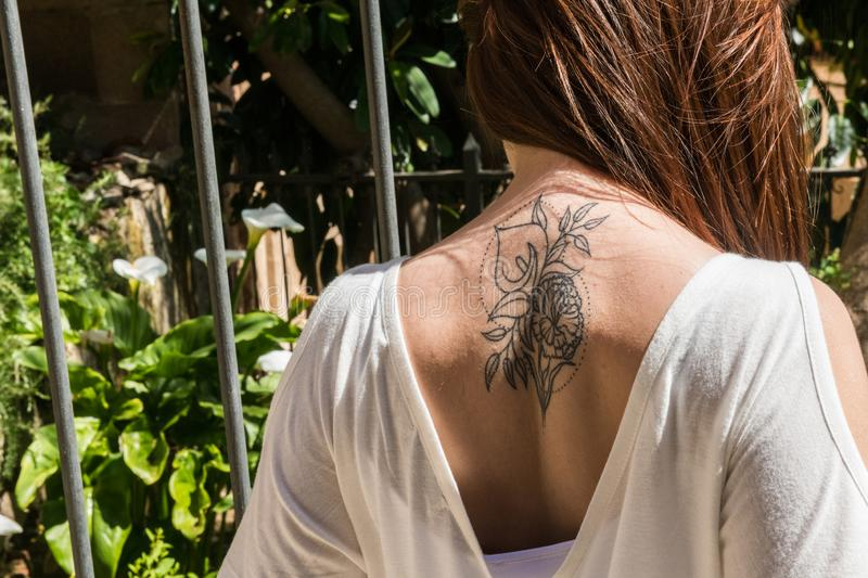 A young red-haired tourist with an Arum-lily tattoo on her back looks at a garden with the same flowers in Caceres. A young red-haired tourist with an original stock images