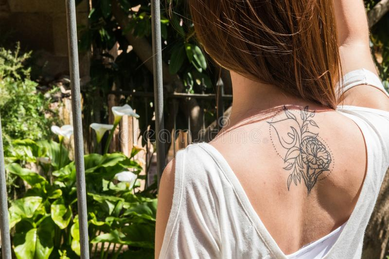 A young red-haired tourist with an Arum-lily tattoo on her back looks at a garden with the same flowers in Caceres. A young red-haired tourist with an original royalty free stock photo