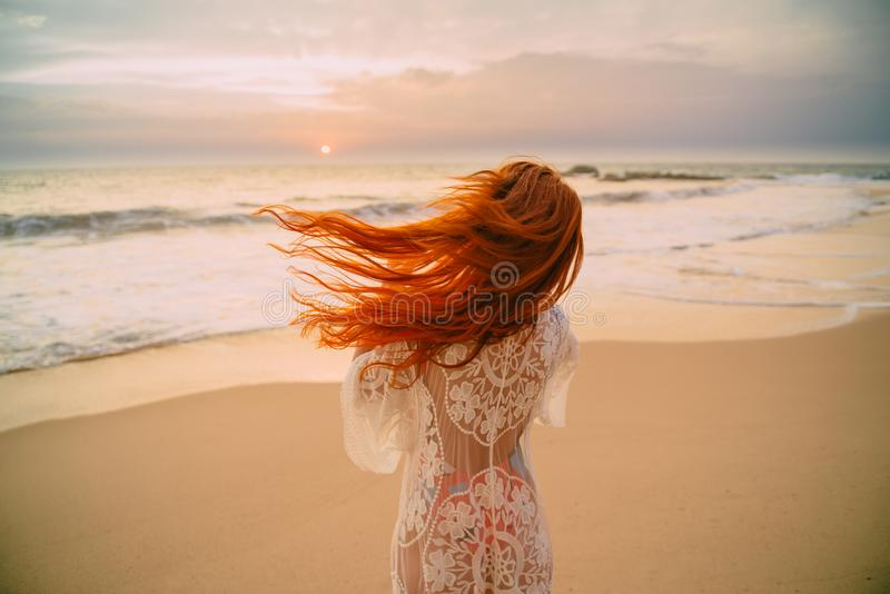 Young red-haired woman with flying hair on the ocean, rear view royalty free stock images