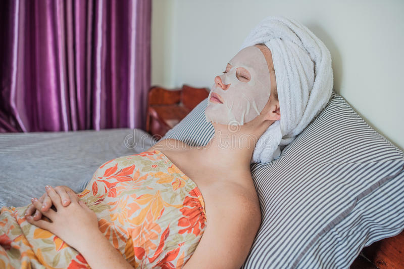 Young red-haired woman relaxing on a bed. Sheet mask on her face royalty free stock photos