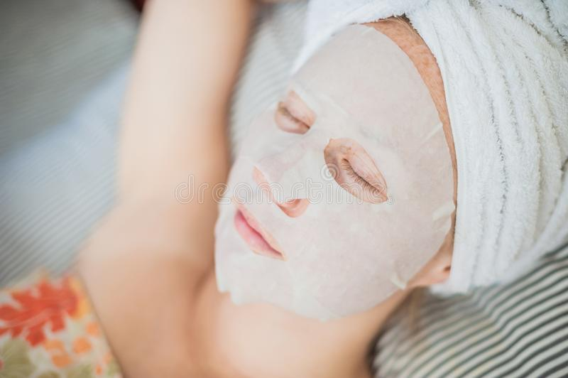 Young red-haired woman relaxing on a bed. Sheet mask on her face stock image