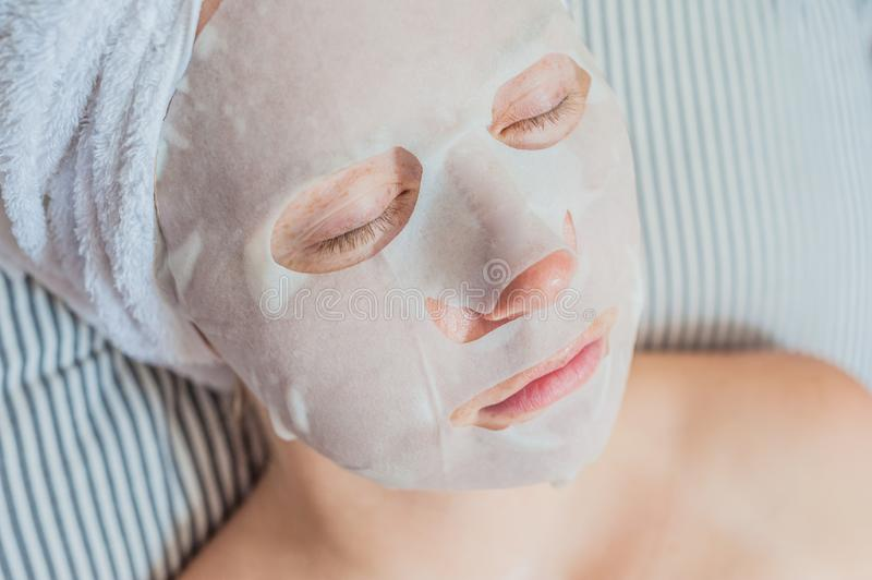 Young red-haired woman relaxing on a bed. Sheet mask on her face stock images