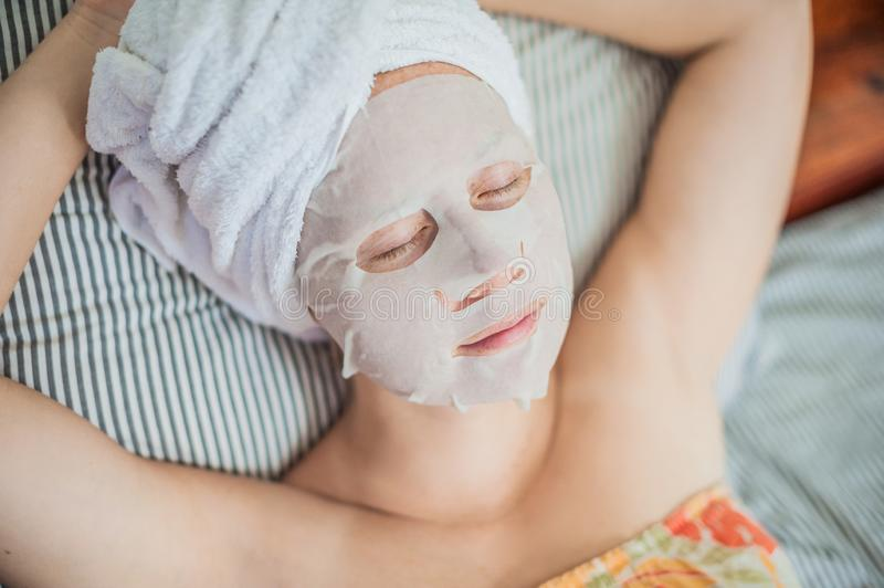 Young red-haired woman relaxing on a bed. Sheet mask on her face stock photo
