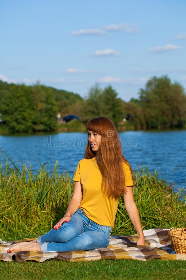 Young red-haired woman resting on the lawn near the lake. Young beautiful red-haired woman resting on the lawn near the lake royalty free stock photos