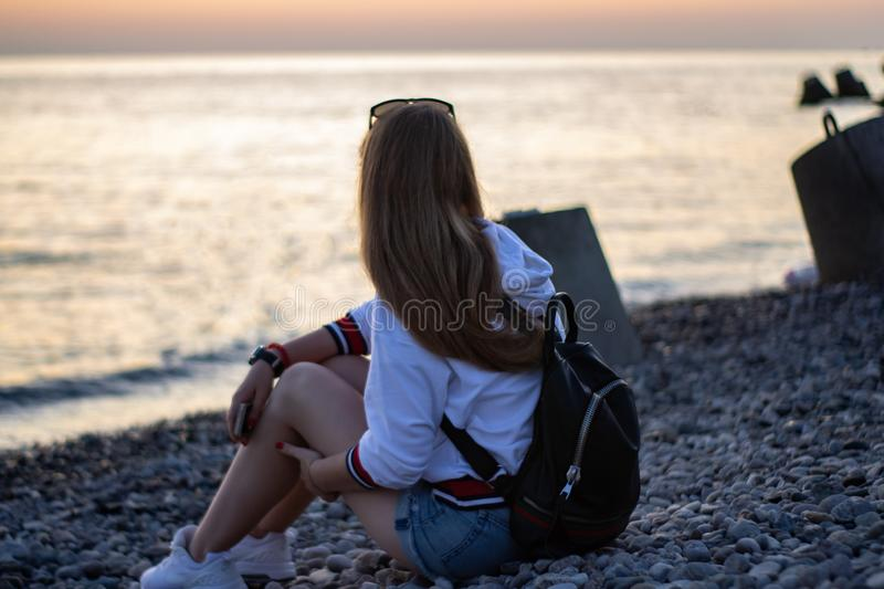 Young red-haired woman sitting on the rocks and watching at the sunset on the sea stock images