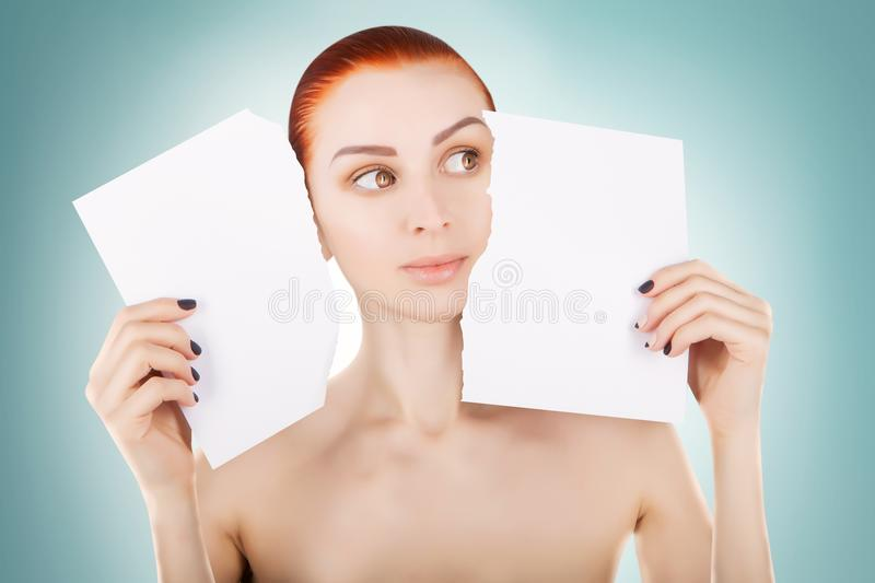 Young red haired woman with white paper, blue background stock image