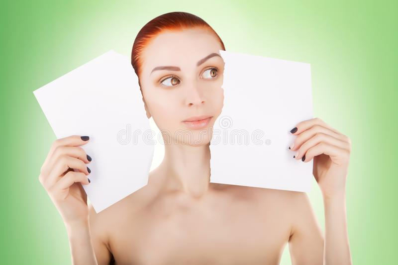 Young red haired woman with white paper, green background stock photography