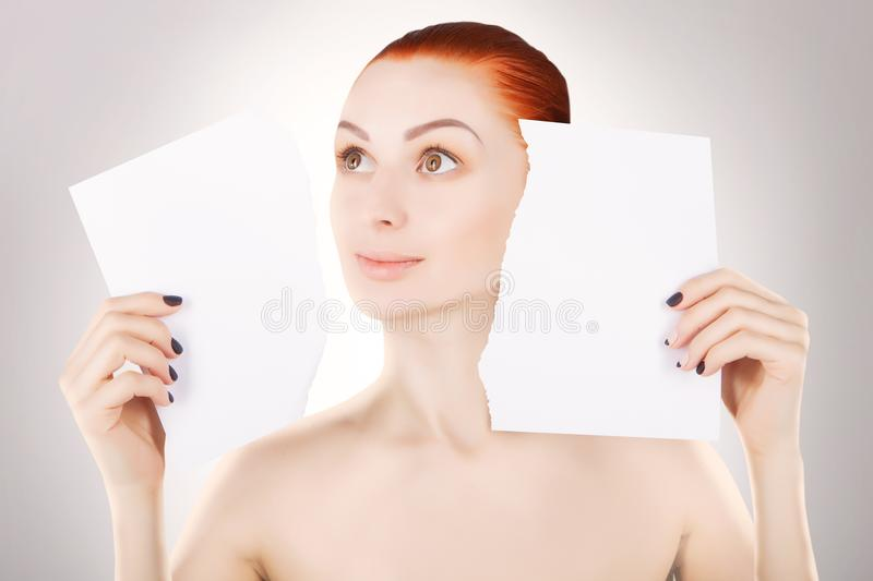 Young red haired woman with white paper, grey background stock photo