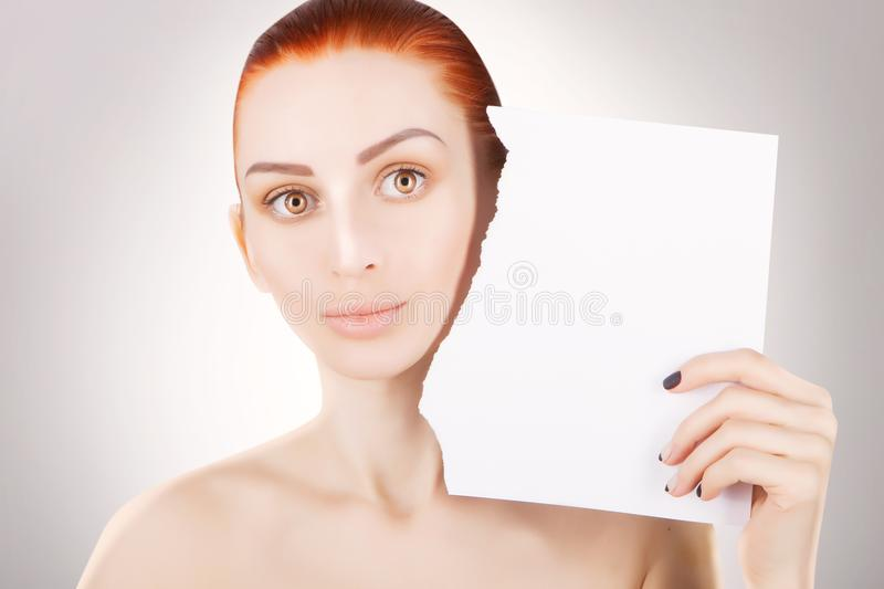 Young red haired woman with white paper, grey background royalty free stock photography