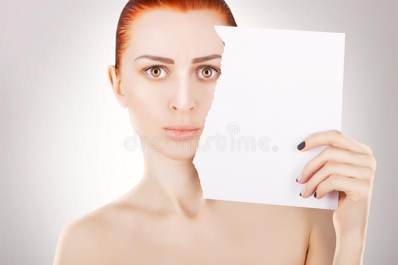Young red haired woman with white paper, grey background stock image