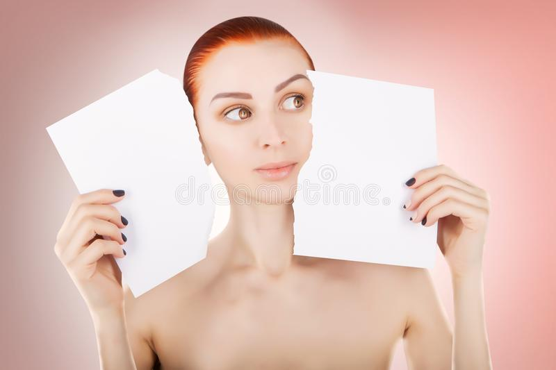 Young red haired woman with white paper, pink background stock photography