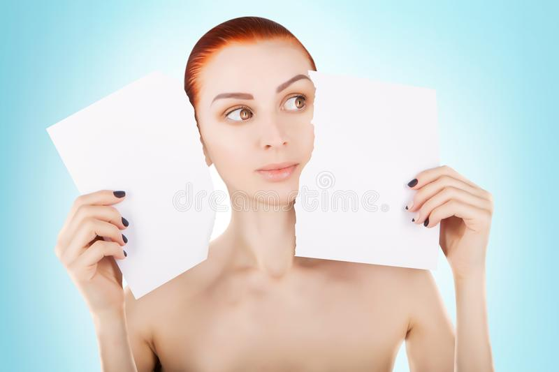 Young red haired woman with white paper, blue background stock photo