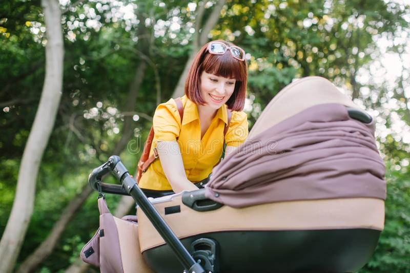A young red-haired woman in a yellow shirt is walking with a small baby in a stroller on a summer bright day in the park royalty free stock photo