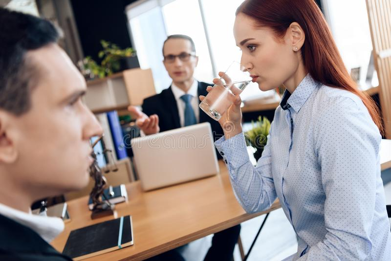 Young red-haired woman is drinking glass of water, sitting next to adult man in divorce lawyer`s office. royalty free stock photo