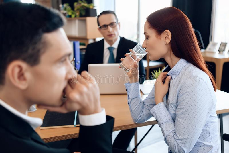 Young red-haired woman is drinking glass of water, sitting next to adult man in divorce lawyer`s office. stock photo