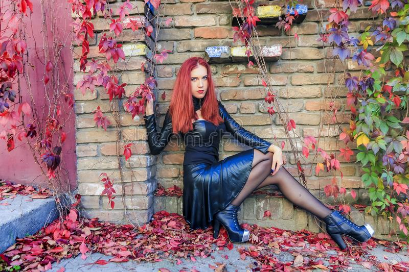 Download Young Red Head Gothic Woman Sitting At The Bottom Of Brick Wall Surrounded By