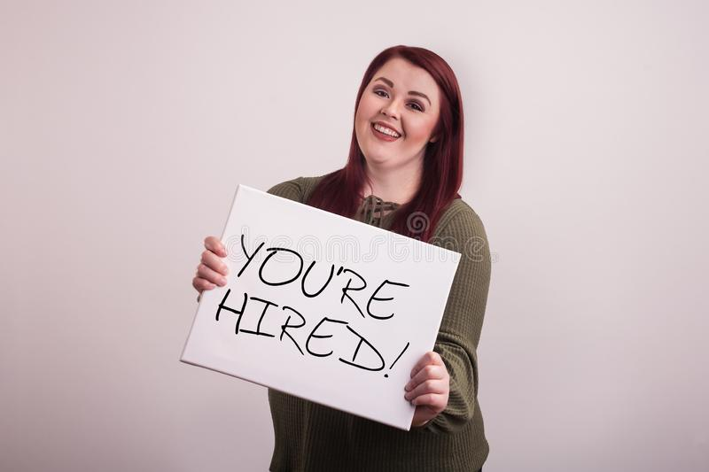 Young female woman holding a message board with You`re Hired written in black ink. Young red headed female woman holding a message board with You`re Hired stock photos