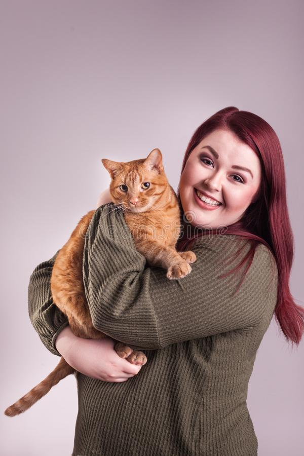Woman holding cute male orange tabby cat smiling. Young red headed woman nice expression holding an unsure male orange tabby cat royalty free stock photography