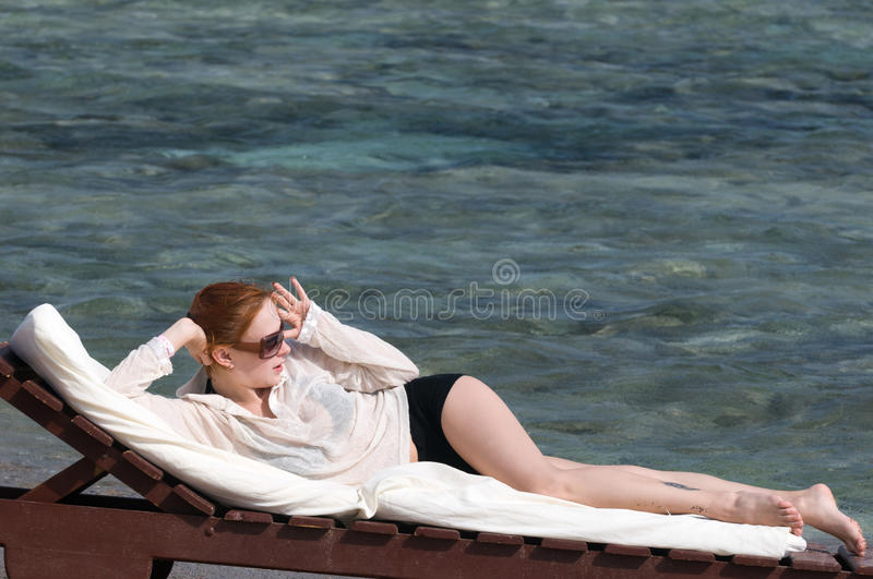 Young red woman sunbathing