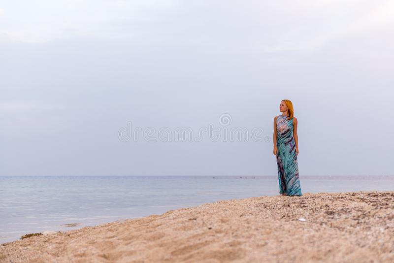 Young red woman on a beach stock photo