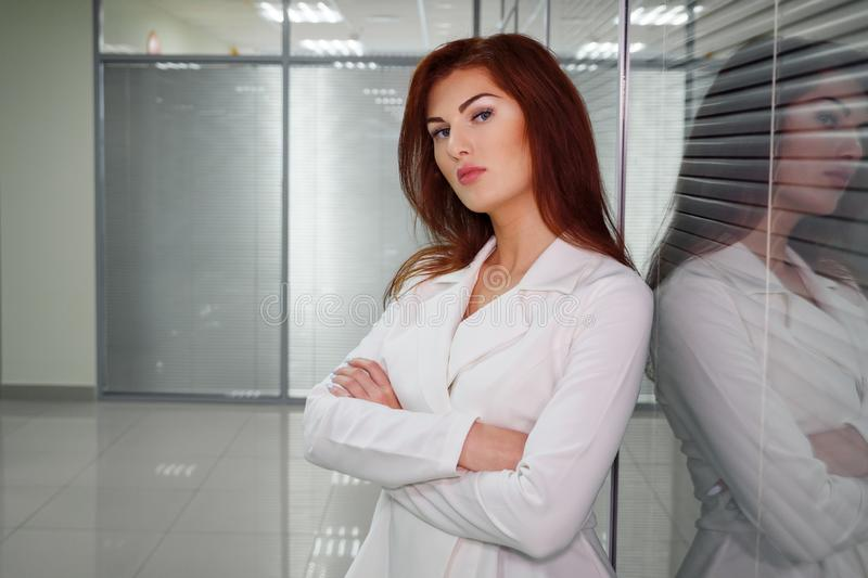 Young redhaired businesswoman in corridor of office looking at camera stock photography