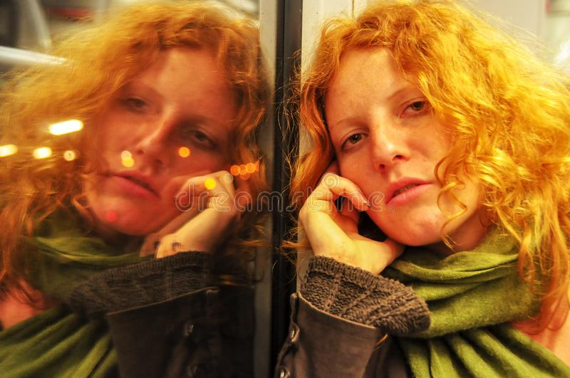 Young redhead beautiful sexy woman sitting thoughtfully in a moving train the portrait is reflected in the window stock photos